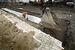 GROOT AMMERS - Aanleg van een rioolgeul van Megatrax op een 30.000 m2 groot bedrijventerrein voor Van der Vlist Speciaal -en Zwaartransport in Groot Ammers. Megatrax bestaat uit restgrond, baggerspecie en mijnsteen, dat verstevigd is met een poeder waardoor grote stevigheid onstaat en het als goedkoop alternatief voor beton kan functioneren als ondergrond. De grond  steunt op in de grond gemaakte heipalen. COPYRIGHT TON BORSBOOM...