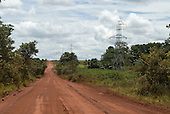 Canarana, Mato Grosso State, Brazil. Rodovia MT020 road; unpaved dirt road of red earth through agricultural land cattle soya sweetcorn and rice fields with little forest cover; new electricity pylons to carry the electricity from the Paranatinga II hydroelectric dam.