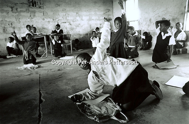 NQABENI, SOUTH AFRICA - AUGUST 20: Bawinile Zulu, age 11, (center) sitting on the floor in class in her school with friends on August 20, 2002 in Nqabeni, a rural area outside Port Shepstone, in Southern Natal Province, South Africa. Bawinilie was raped by a neighbor?s son a couple of weeks earlier in the small village. As a traditional Zulu area, most things are solved through negotiation and compensation. The girl?s father was compensated with two cows for the breaking of the girl's virginity. Bawinilie just started in another school, as the father believes that she might get teased in the nearby school. The 22-year old suspect is arrested and is awaiting trial. South Africa has one of the highest rates of rapes against women and children in the world..Photo: Per-Anders Pettersson/ Agentur Focus.....