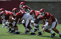 NWA Democrat-Gazette/ANDY SHUPE<br /> Members of the Arkansas offensive line Mitch Smothers (from left), Sebastian Tretola, and Denver Kirkland block Tuesday, Aug. 11, 2015, with tight end Hunter Henry (right) during practice at the university's practice field in Fayetteville.