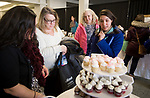 TORRINGTON, CT-011418JS02---Jennifer Aprile, owner of Wedding Cakes Unlimited in Torrington, left, serves cupcakes to Caitlin Lawrence of Bristol, right, as her mother Heidi Clark of Torrington and future mother-in-law, Carolyn Rivard of Glastonbury, look on during the Annual Bridal Event 2018 held Sunday at the Warner Theater's Carole and Ray Neag Preforming Arts Center in Torrington. Lawrence is getting married in October 2019. More than 60 vendors were on hand for the event. <br /> Jim Shannon Republican-American