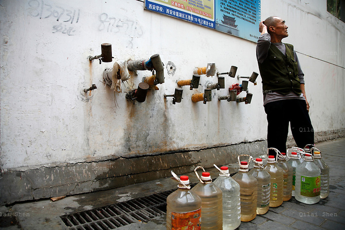 An elderly man carries bottles of water after filling them at a wall full of locked up water faucets in Xi'an, Shaanxi Province, China on Tuesday, 01 May 2007. Each faucet belongs to an individual family living nearby. The availability of clean potable water continue to decrease in china as rivers and lakes suffers from pollution despite the government's call for a sustainable development.