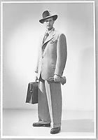 Fashion circa 1940-45 from the Nordic Company. Young man wearing rough tweed suit, white shirt and small patterned tie, in the breast pocket a checkered handkerchief. He wears a hat and coarse shoes. In one hand he holds a pair of leather gloves, in the other a briefcase.