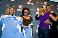 Boston Breakers head coach Tony DiCicco hugs Heather Mitts as Kristine Lilly and Angela Hucles check out their jerseys. The Women's Professional Soccer (WPS) US National Team Allocation Announcement at the Sports Museum of America in New York, NY, on September 16, 2008.