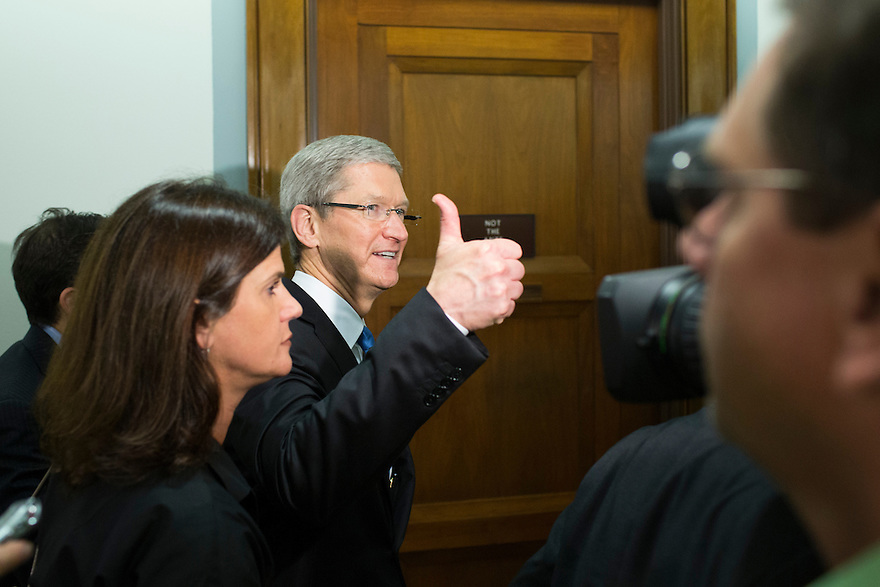 Apple CEO Tim Cook gives the thumbs up as he departs after testifying at a Senate homeland security and governmental affairs investigations subcommittee hearing on offshore profit shifting and the U.S. tax code, on Capitol Hill in Washington. Cook  defended the company's tax record during a Senate hearing where lawmakers said the maker of iPads, iPods and Mac computers kept billions of dollars in profits in Irish subsidiaries to avoid U.S. taxes.