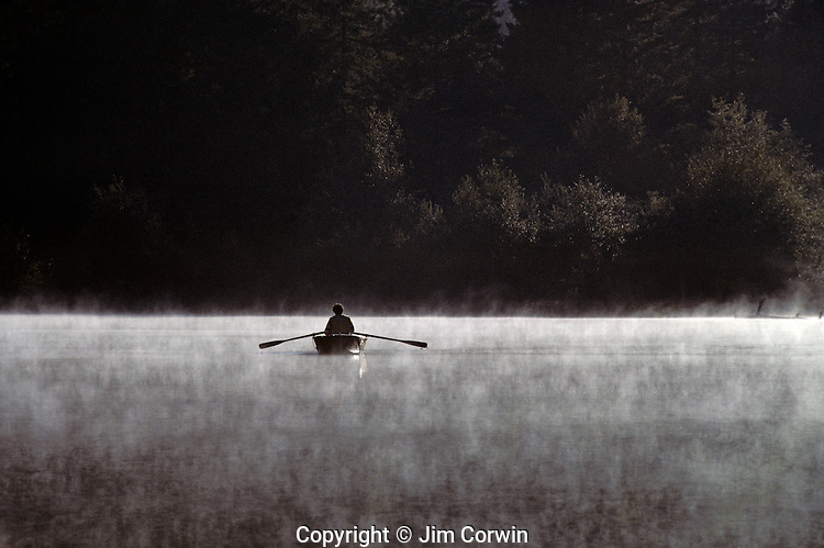 Man fishing in row boat on Lake Mason, sunrise in fog, Olympic Penninsula, Washington State USA.