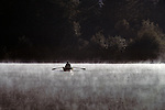 Man fishing in row boat on Lake Mason, sunrise in fog, Olympic Penninsula, Washington State USA.