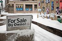 Detroit:  paesaggio urbano d'inverno.Un cartello di vendita appartamenti in una strada innevata e deserta.