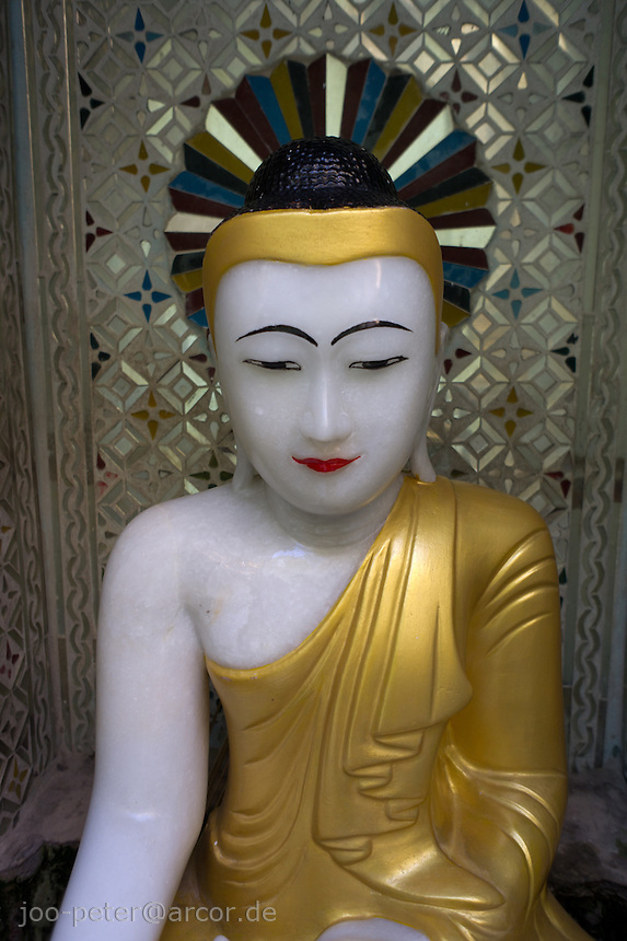 buddha sculpture in small shrine in temple in Mandalay, Myanmar