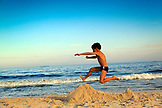 BRAZIL, Rio de Janiero, a young boy jumps over a sand castle at Copacabana Beach