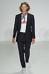 Model walks runway in a navy linen suit, and SIMP tee from the Palmiers du Mal Spring Summer 2017 collection by Brandon Capps and Shane Fonner, with navy floral neck scarf from A.M. Club, at Skylight Clarkson Square on July 14 2016, during New York Fashion Week Men's Spring Summer 2017.