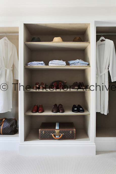 Fabric lined shelving with studded decoration in one of the bedrooms