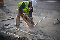 Construction workers install steel conduit pipe underground for utility and traffic signal cables at a road construction site in Westerville, Ohio.