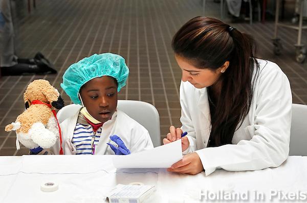 Nederland Amsterdam 2015 11 10 . Teddy Bear Hospital in het AMC  ziekenhuis.  Teddy Bear Hospital (TBH) is één van de grootste projecten van IFMSA-NL. Het TBH is een rollenspel. Dat houdt in dat kleuters van vier t/m zes jaar als 'vader' of 'moeder' hun beer of een andere knuffel meenemen naar een nagebootst ziekenhuis. Geneeskundestudenten spelen voor arts en behandelen de 'patiënten'. Het doel van Teddy Bear Hospital is om kinderen op een speelse manier kennis te laten maken met de gezondheidszorg, om zo de angst voor dokters en het ziek-zijn enigszins weg te nemen. Bovendien leert het medische studenten om te gaan met kinderen en trainen ze hun communicatieve vaardigheden.  Foto Berlinda van Dam / Hollandse Hoogte