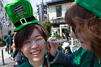 "A Japanese woman gets here face painted at the 27th Saint .Patrick's Day Parade in Omotesando, Tokyo, Japan. Sunday March 17th 2019. Started in 1992 by the Irish Network, Japan, and supported by the Embassy of Ireland,; the parade, along with the ""I Love Ireland Festival"" held nearby is Asia's  largest Irish event."