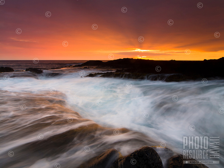 Waves rush into large holes along the rocky coastline of Keahole Point, Big Island; rays from the setting sun through clouds provide a brilliant backdrop.