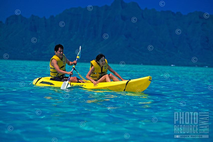 Japanese couple paddiling a yellow kayak in turquoise blue ocean, ahu o laka, Kaneohe Bay, off the island of Oahu