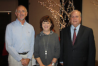NWA Democrat-Gazette/CARIN SCHOPPMEYER Lynda Belvedressi, Courage Award honoree, is joined by Ernest Cate (left) and Jeff Harper at the Peace at Home Family Shelter luncheon Oct. 14.