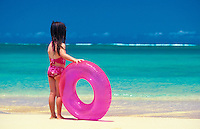 Young girl with pink inflatable tube at beach