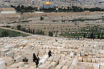 Orthodox Jews visit the old Jewish cemetery on Mt. Olives, Jerusalem. Dome of the Rock is seen in background.