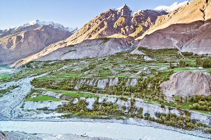 A photo of terraced fields on an alluvial fan next to the Baltoro River. Above are the  snow-capped Karakoram  at dawn in Baltistan, Pakistan
