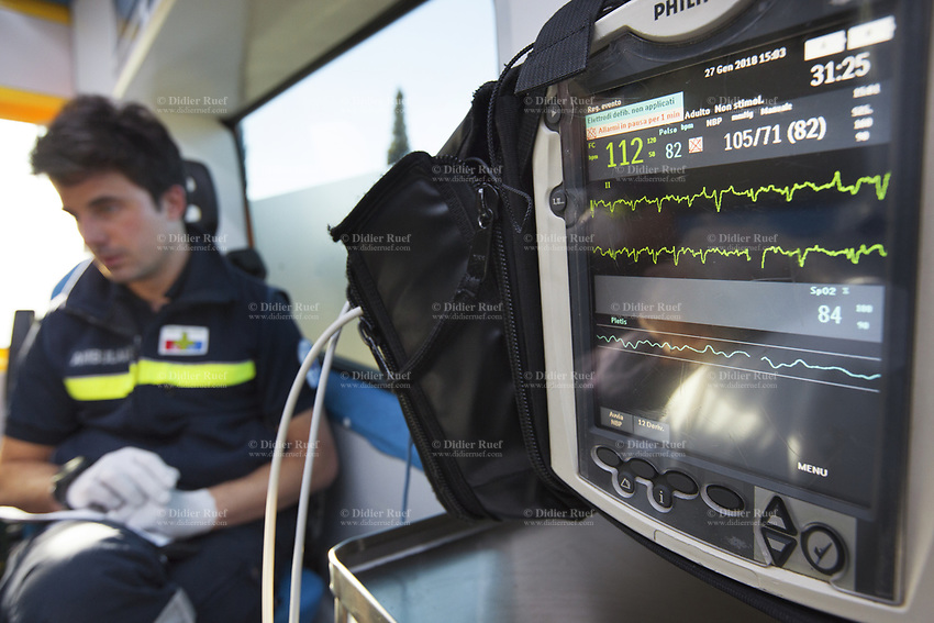 Switzerland. Canton Ticino. Lugano. A paramedic seated in an ambulance during a medical emergency intervention. The paramedic wears a blue uniforms and works for the Croce Verde Lugano. The man is a professional certified nurse. He checks the patient's state with a Philips monitor controlling a set of vital functions, such as  electrocardiogram, blood pressure's measurement, respiratory rate and pulse oximetry (oxygen saturation). The Croce Verde Lugano is a private organization which ensure health safety by addressing different emergencies services and rescue services. 27.01.2018 © 2018 Didier Ruef