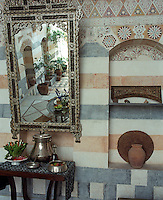 On the covered terrace an inlaid Venetian-style mirror is juxtaposed against a vernacular patterned and striped wall