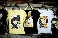 T-shirts depicting large-eyed Asian pop stars hang in a stall in a street market in Shaoxing, Zhejiang Province, China.