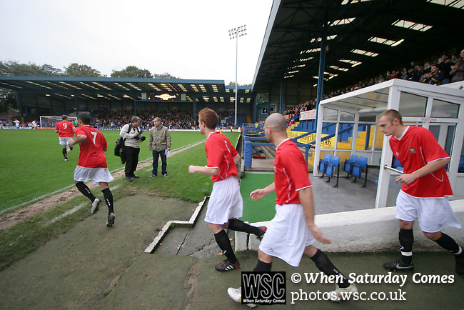 FC United of Manchester 8, Glossop North End 0, 28/10/2006. Gigg Lane, Bury, North West Counties League division one. FC United of Manchester players running onto the pitch before they take on Glossop North End (blue shirts) in a North West Counties division one match at United's home stadium, Gigg Lane, home to Bury FC. The match was staged on People United Day, an event started in 1999 which brought together fans from across Europe to campaign against racism. FC United were formed in the summer of 2005 by supporters of Manchester United in response to the take over of their club by American millionaire Malcolm Glazer and his family. The club entered the football pyramid at the lowest level with the intention to climbing through the leagues. FCUM won the match 8-0, watched by 3257 spectators. Photo by Colin McPherson.
