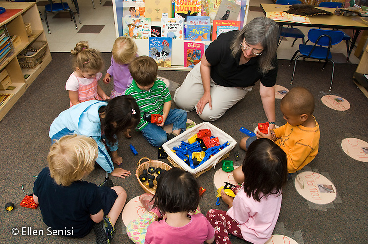 MR / College Park, Maryland.Center for Young Children, laboratory school within the College of Education at the University of Maryland. Full day developmental program of early childhood education for children of faculty, staff, and students at the university..Students (aged 3 and 4) sit together on the floor using a variety of age-appropriate early childhood education materials. Teacher is available for guidance if needed..MR: AH-gPcyc.© Ellen B. Senisi