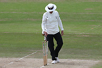 Umpire Mike Burns notices the stumps have been left at odd angles during Nottinghamshire CCC vs Essex CCC, Specsavers County Championship Division 1 Cricket at Trent Bridge on 1st July 2019