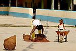 El cacao se va tostando poco a poco, este proceso dura una semana o mas, segun lo que caliente el sol. Aqui vemos como Leila recoge el cacao del patio de la iglesia.  Chuao. Venezuela. © Juan Naharro