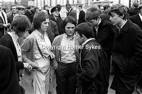Football supports gather outside Chelsea Football Club for a match against Queens Park Rangers. Three young girls with boys, the girls are dressed in the fashion of the time as Bovver Girls, they wear clothes that mimic boys attire, high waisted trousers,  boys shirts and braces.  London England. 1970