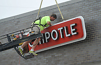 NWA Democrat-Gazette/MICHAEL WOODS &bull; @NWAMICHAELW<br /> Mike Greenleaf with A-Max Signs in Tulsa, works on installing a new sign for the new Chipotle restaurant in Fayetteville Wednesday August 19, 2015.  The New Chipotle is located in the new College Marketplace development on North College.