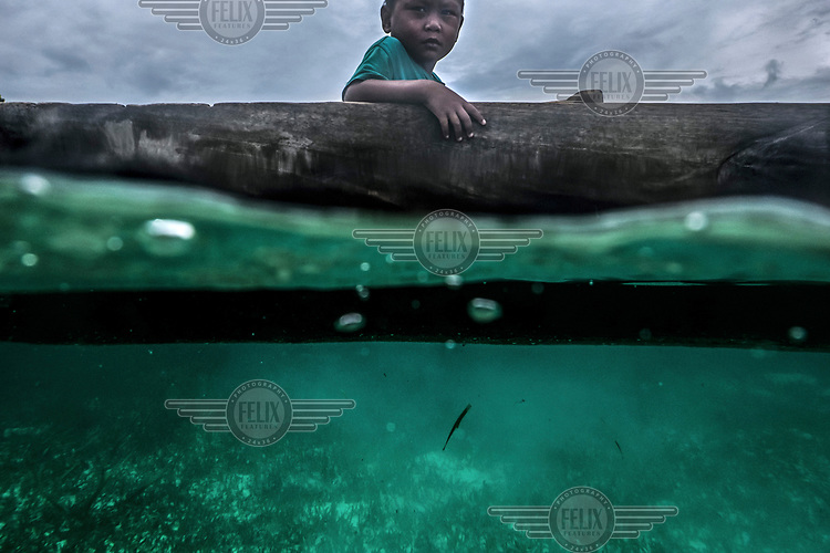 A Bajau child sits in a canoe while his father sets his nets near the island of Malenge in Indonesia.