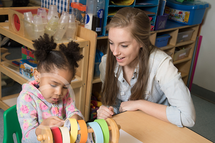 Education Preschool 2-3 year olds therapist or intern working with girl in classroom