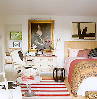 The gilt-framed portrait displayed on the whitewashed tongue-and-groove walls of the pool house is 18th-century English and a matching pair of fumed oak armchairs is covered in a contemporary cowhide