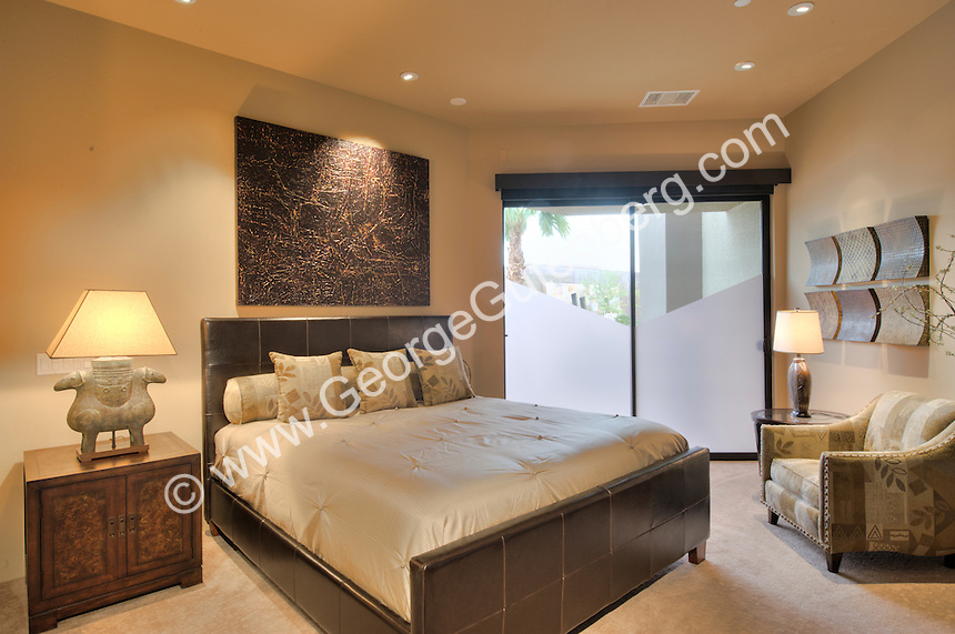 Elegant guest bedroom nicly furnished with art above headboard of bed Stock photo of bedroom