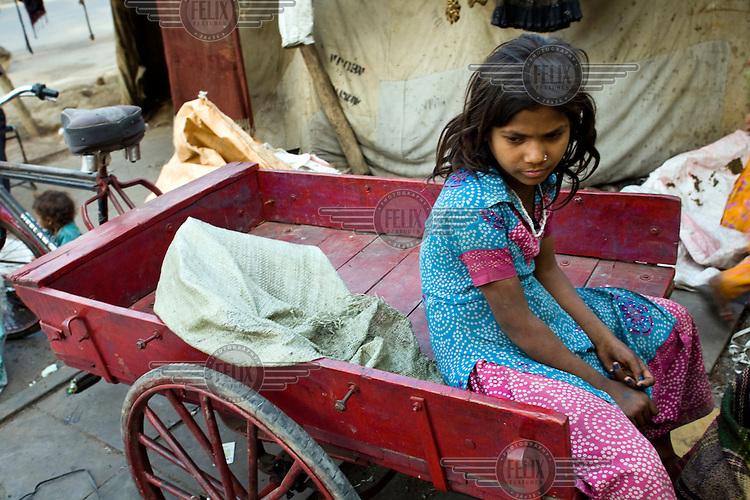 A young homeless girl sits atop a cart used by her family picking up rubbish to resell in Karol Bagh, New Delhi.