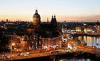 Nederland  Amsterdam 2016 . Amsterdam bij zonsondergang. Links de Nicolaaskerk. Rechts het stationsgebied. Foto Berlinda van Dam / Hollandse Hoogte