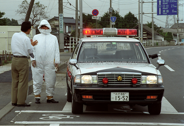 10/2/1999--Tokaimura, Japan..Police wearing radiation suits guard an entrance in the town of Tokaimura after the nuclear accident at the Tokaimura uranium processing plant, about 140 kilometers (90 miles) northeast of Tokyo, where on September 30 at least 70 people were exposed to radiation. Three plant worker died.  Workers at the plant had been suing an illgeal manual to cut corners leading to a chain reaction and explosion....All photographs ©2003 Stuart Isett.All rights reserved.This image may not be reproduced without expressed written permission from Stuart Isett.