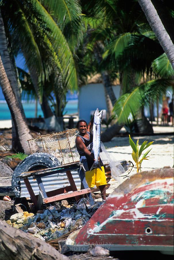Local man holding fresh caught barracuda, Tobacco Caye, Belize