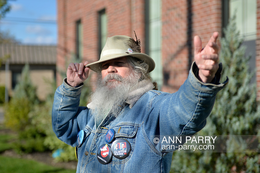 """Merrick, New York, USA. October 23, 2016. FRED S. CHANDLER, 66, of North Bellmore, wearing several political campaign buttons supporting Democratic presidential candidate Hillary Clinton, gestures with hand while talking during rally to demand public water and stop New York American Water (NYAW) rate hike. On denim jacket included buttons for Hofstra University DEBATE 2016 - and """"So My Daughter Knows She Can Be President. Hillary 16"""" - """"TRUMPBUSTERS"""" - """"CLINTON KAINE 16"""" - and Monopoly Man character with """"NEVER TRUMP"""" text."""