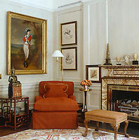 A corner of the Georgian panelled drawing room has a military portrait above a comfortable upholstered chair