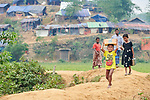 People walk along a path in the Chakmarkul Refugee Camp near Cox's Bazar, Bangladesh. More than 600,000 Rohingya refugees have fled government-sanctioned violence in Myanmar for safety in this and other camps in Bangladesh.