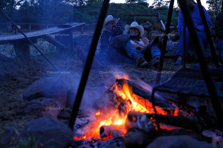 """Guests talk and laugh around the campfire at the Wild Horse Sanctuary. Overnight rides through the ranch end to view mustangs at this rustic site with cabins.<br /> """"It was in 1978 that the Wild Horse Sanctuary founders rounded up almost 300 wild horses for the Forest Service in Modoc County, California. Of those 300, 80 were found to be un-adoptable and were scheduled to be destroyed at a government holding facility near Tule Lake, California. <br /> <br /> The Sanctuary is located near Shingletown, California on 5,000 acres of lush lava rock-strewn mountain meadow and forest land. Black Butte is to the west and towering Mt. Lassen is to the east. <br /> Their goals:<br /> Increase public awareness of the genetic, biological, and social value of America's wild horses through pack trips on the sanctuary, publications, mass media, and public outreach programs.<br /> Continue to develop a working, replicable model for the proper and responsible management of wild horses in their natural habitat.<br /> Demonstrate that wild horses can co-exist on the open range in ecological balance with many diverse species of wildlife, including black bear, bobcat, mountain lion, wild turkeys, badger, and gray fox.<br /> Collaborate with research projects in order to document the intricate and unique social structure, biology, reversible fertility control, and native intelligence of the wild horse."""