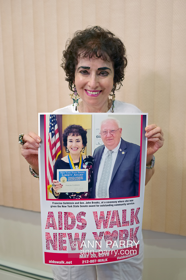 Merrick, New York, USA. May 3, 2018. Francine Goldstein holds special poster AIDS WALK NEW YORK created for her. At top of poster is photo of Sen. John E. Brooks presenting her with NYS Senate Liberty Award.