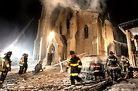 (1/18/05  Jamaica Plain, MA)  Fire at the First Baptist Church of Jamaica Plain. Firefighters evaccuate the building at right  as a new line is added to fight the fire at left. (HC2D0843.JPG Staff photo by Matthew West.  Saved in Wednesday).