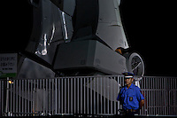 A security guard stands next to a life size model of a Gundam RX78 model, standing18 metres tall and weighing 35 tons, on display in Shiokaze Park in Odaiba to commemorate  30 years of the popular toy is also being used to draw attention to Tokyo`s 2016 Olympic bid. Odaiba, Tokyo August 14th 2009