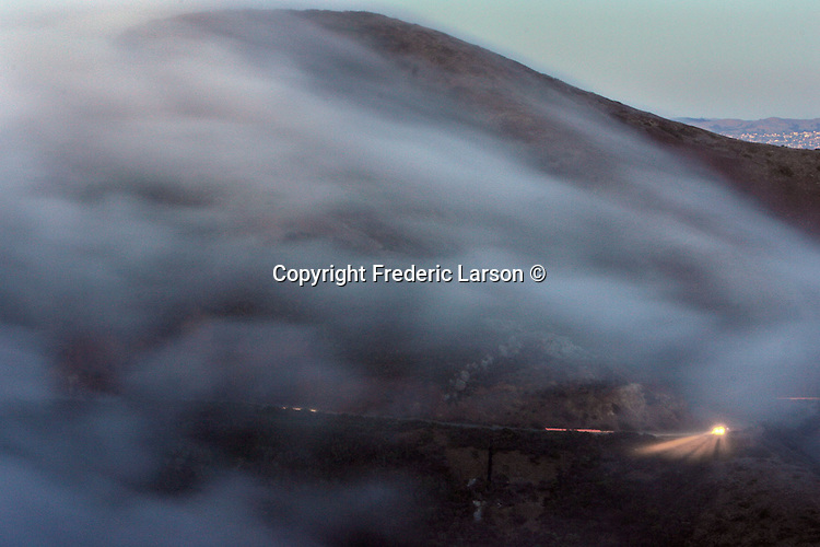 The San Francisco fog slowly rolls into the Gate down the Marin headlands under the Golden Gate Bridge during the evening twilight hours.